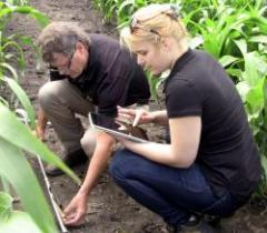 Phillip R. Owens, from left, Purdue University associate professor of agronomy, and doctoral graduate Jenette Ashtekar, compare a soil sample in an auger to a functional soil map on a digital tablet. The function soil mapping technology is being commercialized by Agsoil Analytics, which is using the technology to help farmers improve crop management and yields, by better understanding the functionality of their soil.